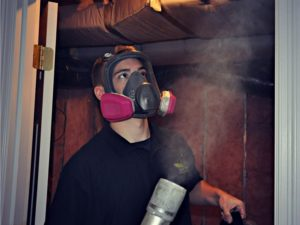 masked man removes odor from wall insulation in Roanoke