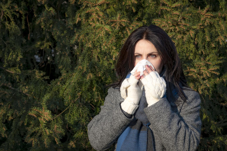 woman with tree allergy blowing her nose by pine tree